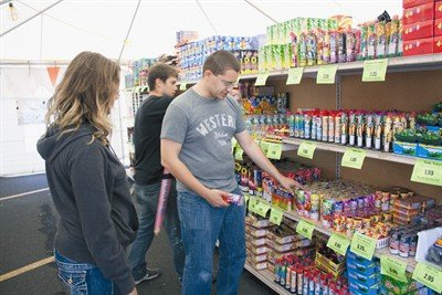 Aaron Schomus (left) and his father, Brian, browse the shelves at BoomTown Fireworks on Friday evening looking for the perfect elements for their home display.