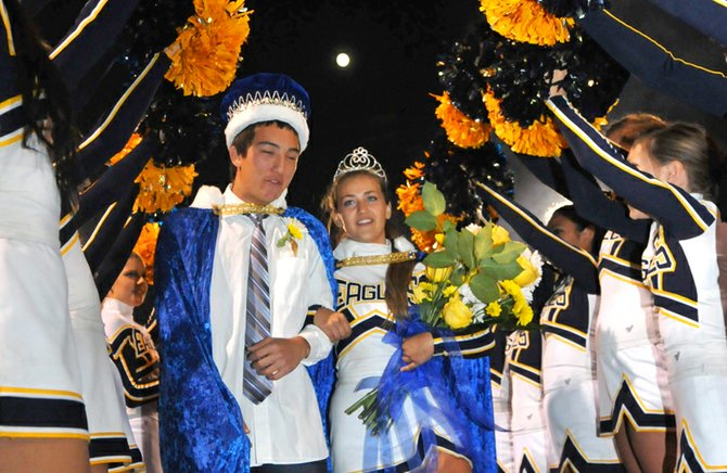 Under an archway of cheerleaders' arms, 2012 Hood River Valley High School homecoming Queen Savvy Adams-Ronk and King Austin Kiyokawa begin their reign after being crowned Friday night during halftime of the Eagles game against St Helens.
