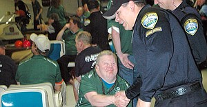 ATHLETE Keith Dunn congratulates Officer Mike Martin for a good frame during Bowl with the Cops at Orchard Lanes.