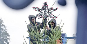 Christmas time is right around the corner, as evidenced by Hood River's downtown Christmas tree. Pictured here are Alex Fuller and Dennis Miller of Hollywood Lights Tuesday  installing some of the roughly 4,000 lights that will brighten up town for the next several weeks starting Friday evening with a festival and holiday parade.