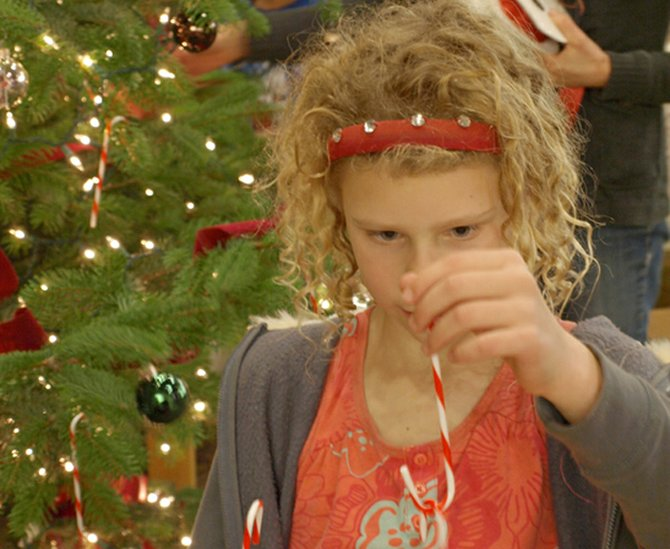 "Zan Lapp plays with plastic candy canes as she prepares to hang them on the Hood River County Library's Christmas tree Tuesday during its ""Charles Dickens Week"" kickoff party. Wednesday the library held a family movie night, Thursday, a discussion of ""A Christmas Carol,"" and Saturday the celebration ends with ""Mr. Fezziwig's Holiday Ball,"" 6:30-8:30 p.m., with food, live music and dancing. Come dressed as your favorite Dickens character and win one of two prizes (one adult and one child) for best costume. The CAST theater group will also perform a scene from its upcoming production of Dickens' ""A Christmas Carol,"" which opens Dec.6."""