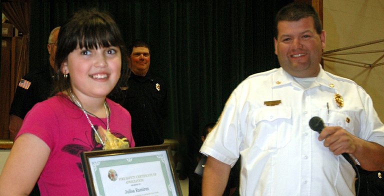 Julisa Ramirez, 8, accepts her Hero Award from Mike McCafferty, Parkdale fire chief, in Friday's assembly.