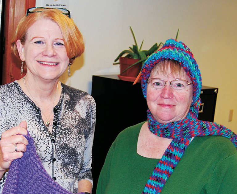 Creative Community – Executive Director Rita Rathkey, left, joins counselor Katie Maple in displaying one client's hand-knit scarves and hats. Adding this new Heights location to its Pine Grove facility, Opportunity Connections is creating an in-town presence to help its disabled adult clients develop work and community networks.