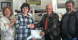 Flight scholarship recipient Eric Hamada (holding certificate) is pictured in front of the General Airways display at WAAAM with (from left) Judy Newman, museum director, Dale Harris, Callas Trust trustee, and Scott Gifford, owner of Classic Wings Aero Services.