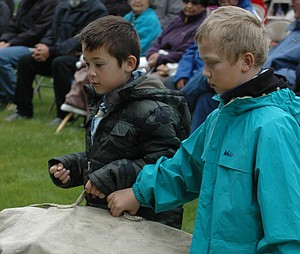 "CUB Scouts from Troop 378 Austin Marquez, left, and Jack Wilson carry a duffel bag during the reading of ""Sea Bags in the Rain."""