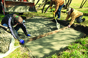 Conducting the concrete finishing work for the tee box at hole two are (L-R) Chris Parrish, Norm Rice and Kevin Asker.