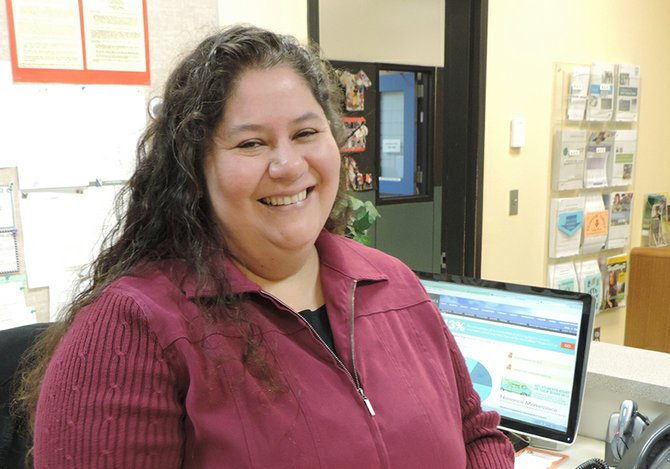 Lucy Marquez greets visitors with a smile as she manages a variety of critical paperwork including alphabetizing student four-year academic plans.