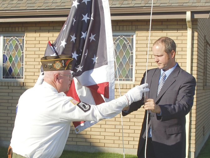 David Humpherys of Valley Hills Funeral Home in Sunnyside receives help yesterday, Thursday, from the Lower Valley Honor Guard in dedicating a new flag for the funeral home's new location on 16th Street, formerly the Sunnyside Christian Reformed Church building. Sharing in the honors with Humpherys is Curt Nealen, the Lower Valley Honor Guard's officer of the day.