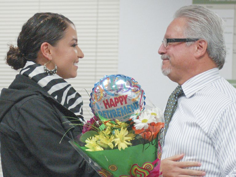 Isla Garibay gives her father, Lorenzo Garza, flowers and a hug during a celebration of his 15 years serving on the Sunnyside School Board. Garza resigned to seek a staff position in the district. His seat will be filled by the winner of next week's election.