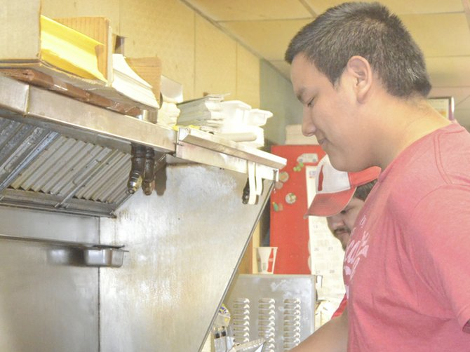 Felix Angiano provides service with a smile at Eli and Kathy's in Grandview, whether cooking up burgers or greeting customers at the counter.