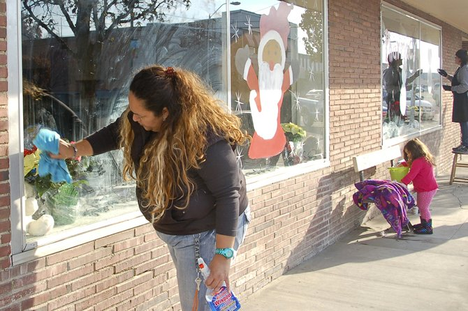 "Sunnyside downtown storefront windows are beginning to look a lot like Christmas. This past Monday afternoon, Sunnyside window painter Paola Guzman began the process of cleaning the windows of the former H&H Furniture building at the corner of East Edison Avenue and South Sixth Street. ""We want to win the Sunnyside Chamber of Commerce's window decorating contest,"" said building owner Bill Capron. He said the storefront will be open Saturday, Dec. 7, just in time for Sunnyside's 25th annual Lighted Farm Implement Parade. For more details on the window decorating contest, call the chamber office at 837-5939."