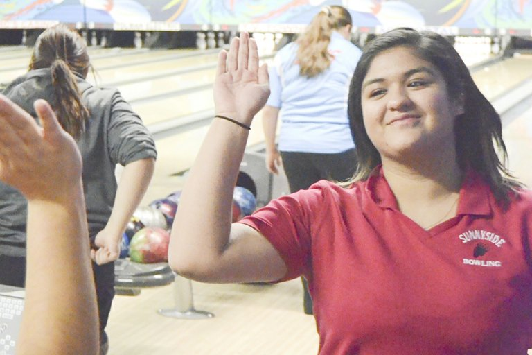 SHS senior Thalia Borja receives a high five from a teammate after rolling a strike in yesterday's match against the visiting West Valley Rams. Borja had games of 137-113 for the Lady Grizzly bowlers.