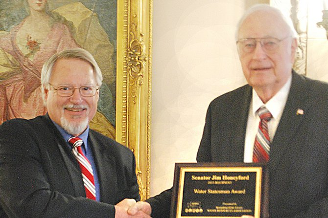 Mike Schwisow, government relations consultant with the WSWRA, presents Sen. Jim Honeyford with the 2013 Water Statesman Award at the Davenport Hotel in Spokane.