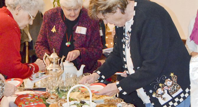 Sunnyside's Nouvella Club members, keeping in the spirit of Christmas giving, yesterday (Thursday) held their annual Christmas tea, during which they enjoyed numerous homemade finger foods. Below, Sunnyside firefighters Mike Beckwith (left) and Bill Harris receive gifts for local children in need. Nouvella Club Social Coordinator Pat Hull presented the gifts. Other organizations receiving donations at the tea included Lower Valley Crisis and Support Services, and the Lower Valley Pathway Association. At right, newly inducted Nouvella Club member Barbara Christensen enjoys the gathering.