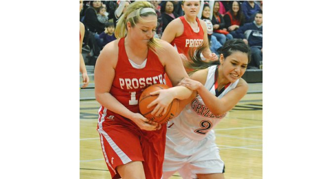 Prosser's Karlie Lusk grips the ball tightly as Sunnyside's Mireya Herrera struggles to come up with a steal in last Friday's prep hoop game on the Lady Grizzlies' home floor.