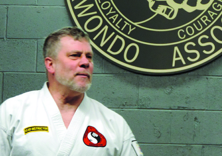 GEORGE EVANS watches his charges as they work on vigorous, yet precise, Tae Kwon Do moves.