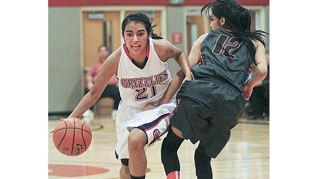 Sunnyside freshman Emilee Maldonado pushes her way past Alexis Perez of Davis in Friday's hoop game on the Lady Grizzlies' home court. Maldonado scored a game-high 17 points for Sunnyside.