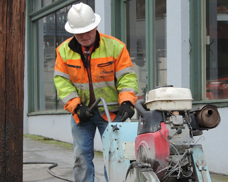 CRESTLINE Construction employee Craig Rohan cuts concrete on State in front of Sheppard's Monday afternoon.