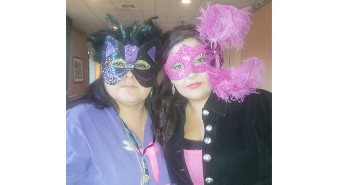 Teri Alvarez-Ziegler (L) and her daughter, Marlee, don Mardi Gras masks in anticipation of the Mardi Gras Pageant to benefit St. Joseph's Church in Sunnyside.