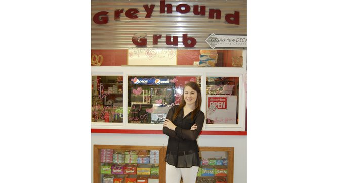 Miranda Ebbelaar stands in front of the DECA store, Greyhound Grub, at Grandview High School. Thanks in part to Ebbelaar's work over the past year, the store has earned a gold level certification from the international organization.
