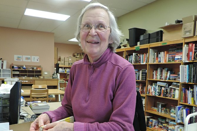 Mary Deaville relabels books in the workroom of the library.