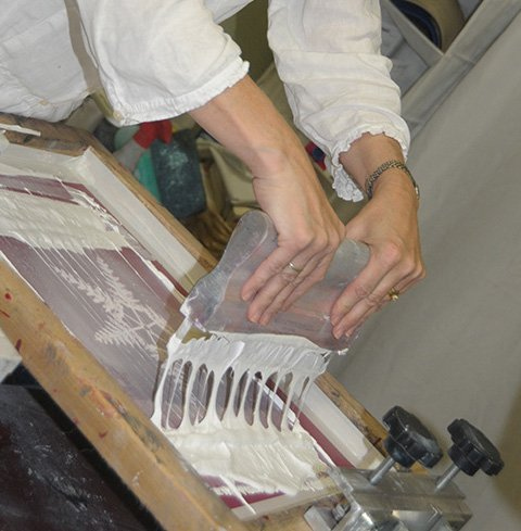 "Laurie Rockwell works on a screen print in her Grangeville Main Street business, ""Imprint Graphics."""