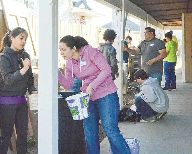 More than 150 volunteers spruced up homes in Sunnyside as part of the Loving Sunnyside Initiative. In the foreground are (L-R) Sierra Equihua and Melanie Castilleja.