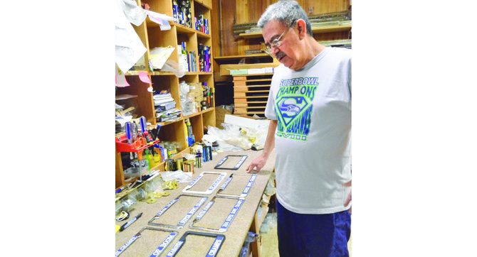 Rudy Guzman, owner of Classic Trophies in Granger, looks at different Seahawk license plate frames he has been creating for Lower Yakima Valley residents.