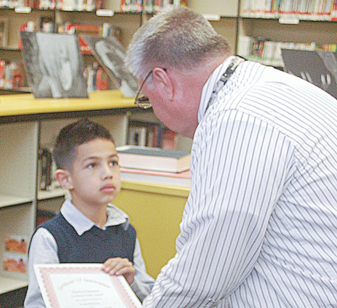 Grandview's McClure Elementary School second grader Evan Benitez listens carefully to Grandview School Board Chairman Paul Jepson following Benitez's leading of the flag salute during opening ceremonies held at Monday night's Grandview School Board meeting.