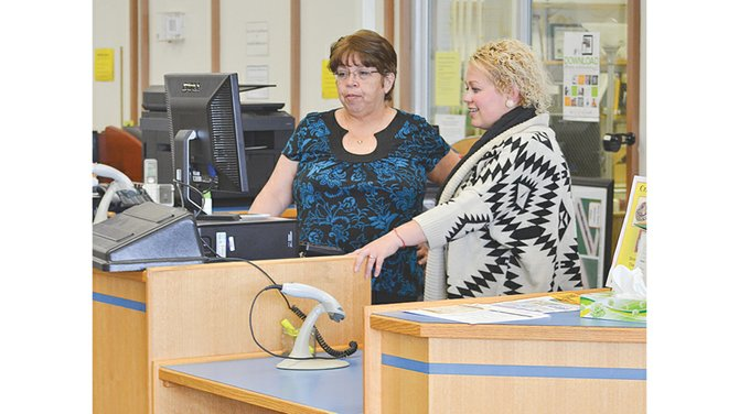 An engineering report will be conducted prior to the remodel, and one of the areas to be examined is possibly changing the layout of the Sunnyside Library circulation desk to improve service for patrons. Pictured is Marcelina Ortega, lead librarian for the Sunnyside Library (L), with regional library spokesperson Charlotte Hinderlider.