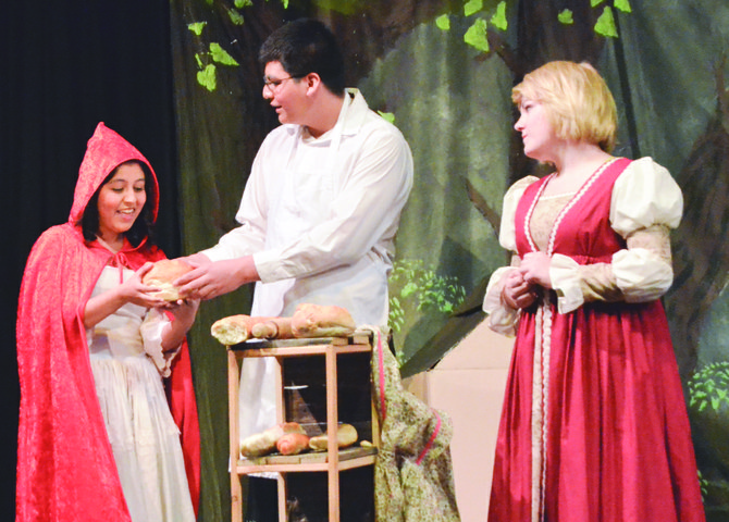"The baker (Isaac Garcia) gives Little Red Riding Hood (Inez Torres) bread for her grandmother as his wife, Emma Perez, looks on during last Saturday's Grandview High School drama club's spring production of ""Into the Woods."" Additional performances are slated for this coming Friday and Saturday."