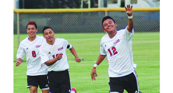 Sunnyside's Alexander Marin (12) celebrates with teammates after he scored the opening goal last night in a 3-0 Regional playoff victory over Kamiakin. Joining in the festivities are Luis Licona (L) and Enrique De La Cruz, who assisted Marin on the goal. Marin had a hand in all three of Sunnyside's scores, as he was taken down in front of the Kamiakin net to earn the Grizzlies a penalty kick and as time expired assisted Francisco Quiroz on the final goal.