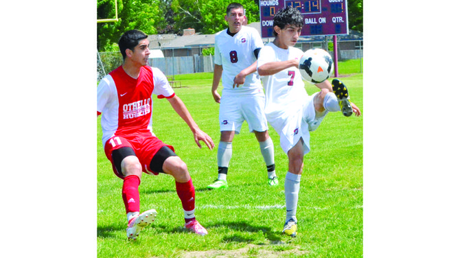 Victor Valencia of Grandview boots the ball to deliver a pass as an Othello defender and Greyhound Lizardo Perez anticipate the action.