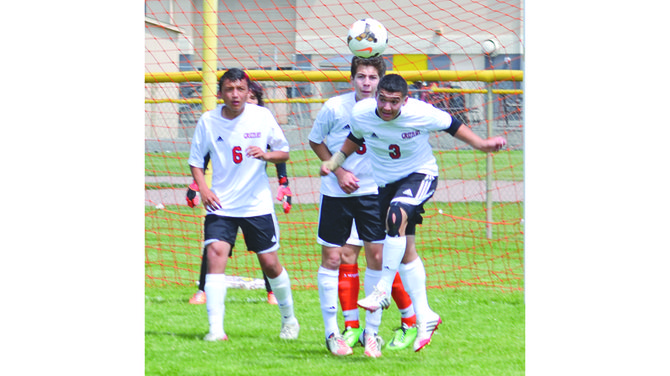 Grizzly defender Humberto Galvan (3) heads the ball away from the Sunnyside goal with teammate Jesus Marquez (6) standing nearby.