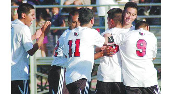Noe Meza, facing camera, receives celebratory hugs from Sunnyside teammates after scoring the winning goal in Tuesday's loser-out State play-off match. Pictured joining the celebration are Misael Vasquez (11) and Christian Chavez (9).