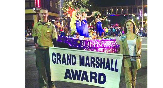 "The Miss Sunnyside community float ""Egyptian Treasures"" earned the Grand Marshall Award last Saturday at the annual Spokane Lilac Festival Torchlight Parade.  Parade volunteers carry the award banner in front of the float. Pictured are (L-R) Princesses Ashley Davis, Leah Diddens and Tiana Perez. Hidden from view atop of the float is Miss Sunnyside Alyson Spidle."