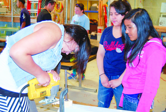 Sunnyside High School student Danielle Samaniego (left) uses a jigsaw to make cuts to a wood block as Harrison students Izarely Jimenez and Mikayela Vega watch. The finished Pinewood Derby cars will be put into action tomorrow, Wednesday, at Harrison Middle School.