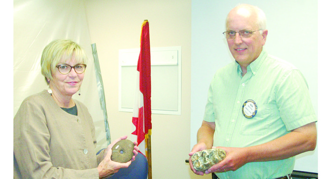 Executive Director Julie Stein of the Burke Museum, Washington's only museum of natural history and culture, shares information about some of the fossils found in the Yakima Valley, with Sunnyside Daybreak Rotary President Nick Friend. Stein was the guest speaker at the Rotary Club meeting today.