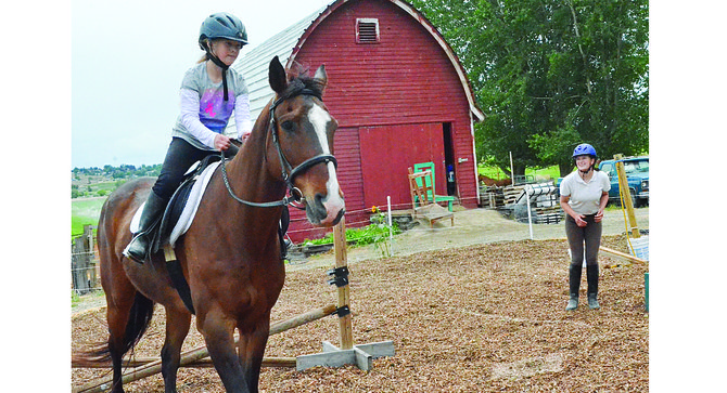 Kirsten Scott (right) gives sister Rachel direction as the younger of the sisters practices riding Reno.