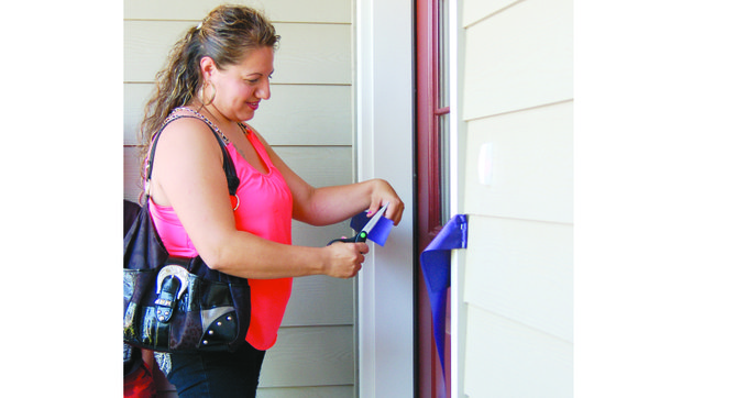 Silvia Lopez cuts the ribbon on the door to her new home after receiving the key from Neri Tellez, the construction coordinator who also helped teach her how to build her home. Tellez said the women worked on their own future homes for seven months, doing 65 percent of the work.