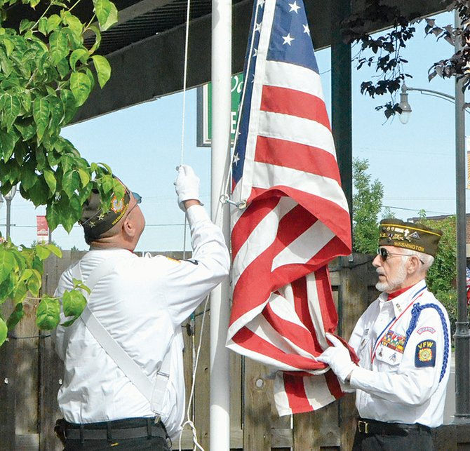 Bill Ingram and Joe Gordon raise the flag at Grandview's Stokely Square during the annual 4th of July flag raising ceremony.