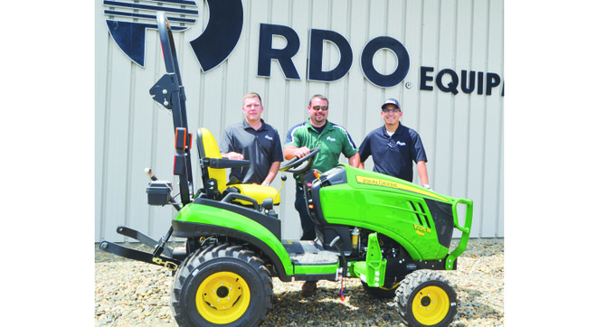 Standing with the tractor that will pull a custom-made trailer built by K and D Machinery are RDO Equipment Co. employees (L-R) Ike Malson, Travis Hanger and Eric Garza.