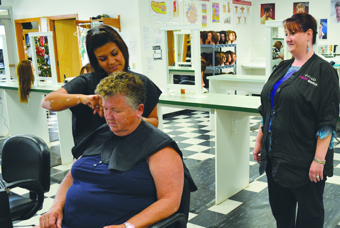 Kristen Chester, at right, a floor instructor at Sunnyside Beauty Academy observes student Maribel Rojas providing a haircut for Kathy Williams of Outlook.