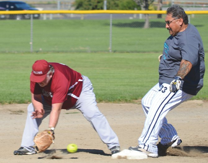 Bob Sarmiento of the local Old Timers club hustles into second base ahead of an errant throw in last Saturday's opening contest. It was part of a five-run, third-inning rally for the Lower Valley team capped by an inside-the-park grand slam by Pete Alvarado.