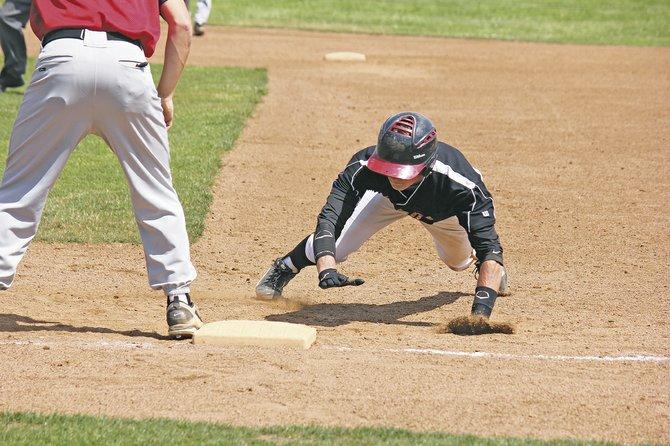 Demarini Dirtbags' shortstop Andy Armstrong slides back to first base to avoid being thrown out on Sunday.