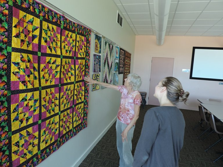 PARKDALE's Robbie Lapp points to a quilt feature while visiting the display with library assistant director Rachael Fox. The quilts serve as a preview of the Quilters Guild Show Aug. 14-16 at Hood River Middle School.