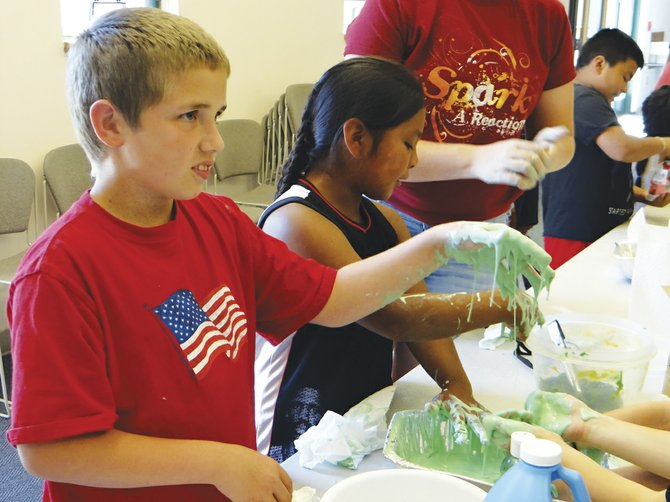 Mikie Stokes-Hime, 10, gets his hands slimy at Independence Public Library's summer program of Grossology. The goop squished between his fingers and dripped off into a box on the table. Other activities included identifying animal poop.