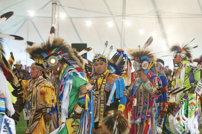 A dancer (top photo) watches the singers and drummers performing as he participates in Friday night's grand entry dance at the Confederated Tribes of Grand Ronde Contest Powwow. The event  ran Friday through Sunday in Grand Ronde.