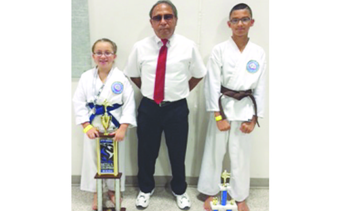 Two Sunnyside youths last Saturday performed well during the Battle on the Columbia Martial Arts Tournament in Richland. Areesa Rodriguez (L) placed first in the kata division and third in the sparring division. Mark Aranda (R) earned second place honors in the kata division. Aranda and Rodriguez will be going into the eighth and second grades, respectively, this fall. They are pictured with instructor Rocky Gonzales, a martial arts grand master.
