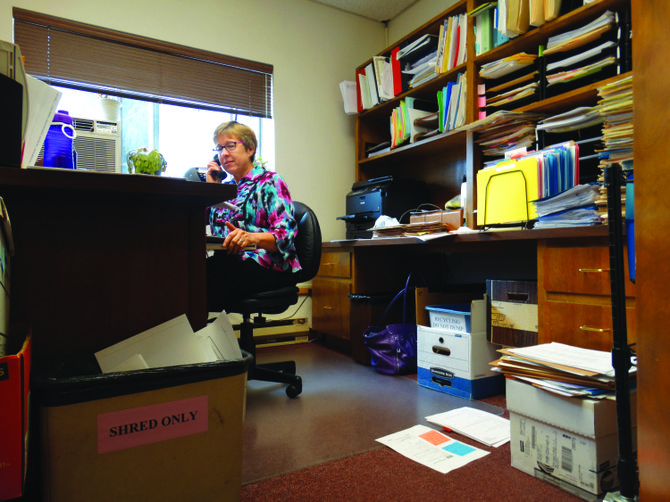 Emily Markus works in a cluttered office at Monmouth City Hall. Space is at a premium throughout the building, where boxes of files sit under desks, in hallways and on the floor.